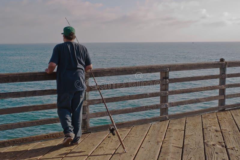Ein Mann, der von einem Pier über dem Pazifischen Ozean fischt stockbilder