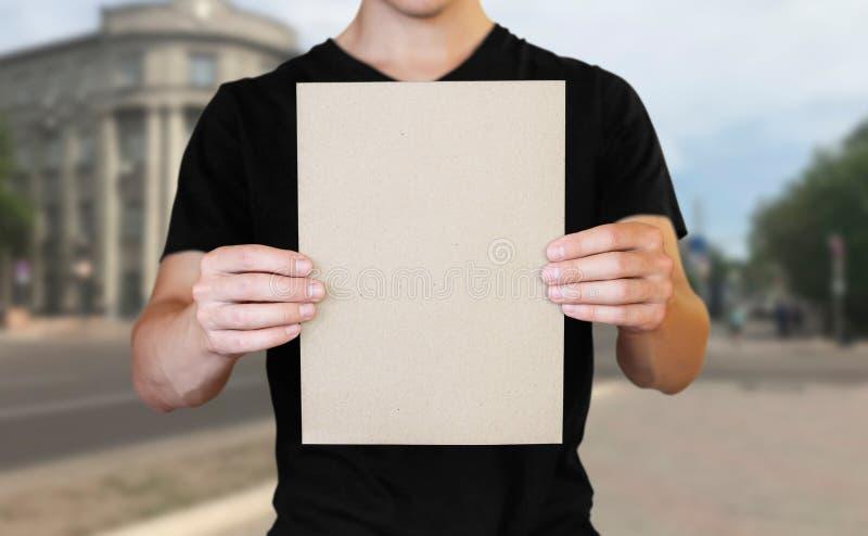 Ein Mann, der ein wei?es Blatt Papier h?lt Halten einer Broschüre Abschluss oben Der Hintergrund der Stadt lizenzfreie stockfotos