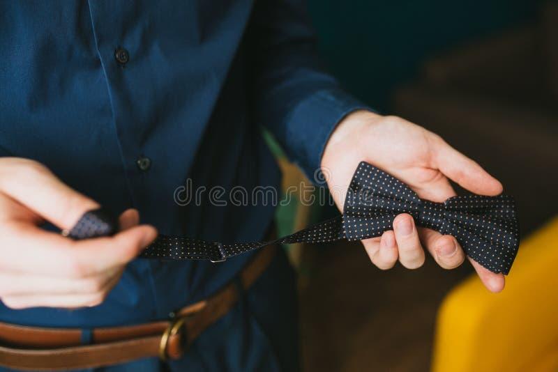 Ein Mann in einem blauen Hemd hält eine Fliege in den Tupfen Heiratender stilvoller Zusatz stockfotos