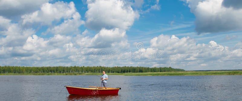 Ein Mann in einem Boot, in der Mitte des Sees, hält eine Angelrute, um einen großen Fisch, gegen einen schönen Himmel zu fangen stockbild