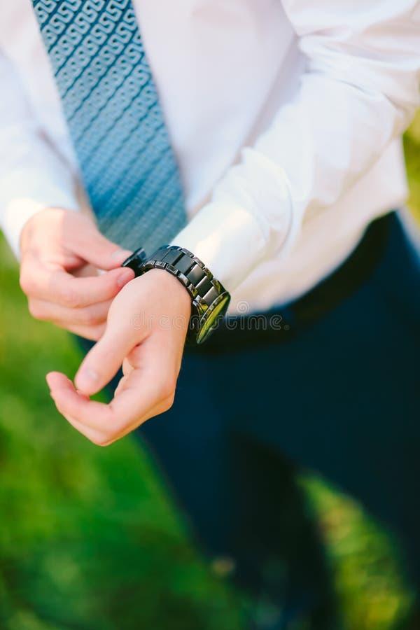 Ein Mann in einem Hemd und in einer Bindung, setzt seine Hand auf die Uhr Hochzeit GR stockbild