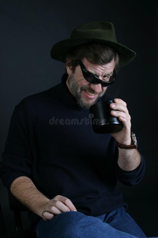 Ein Mann in einem Hut mit einem Cup lizenzfreie stockbilder