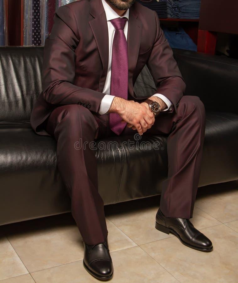 Ein Mann in einem klassischen Anzug sitzt auf einem schwarzen ledernen Sofa, linke Seitenansicht stockfotos
