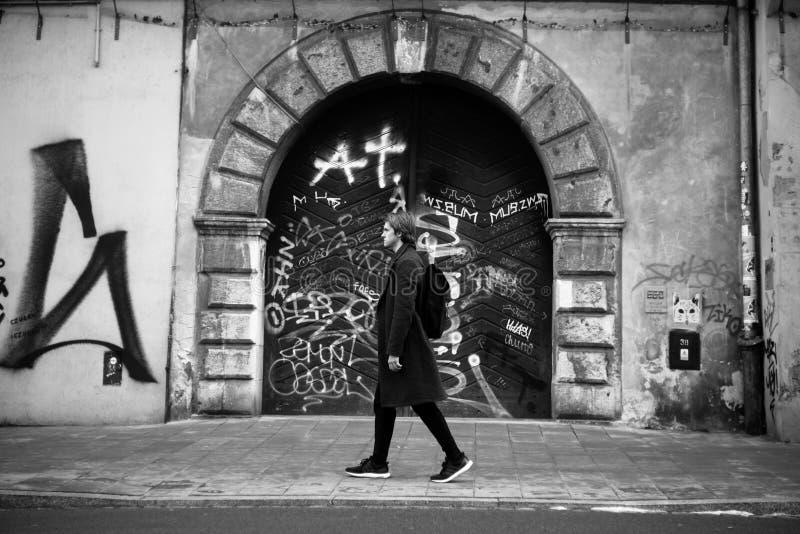 Ein Mann in einem langen Mantel, Reisen zum alten Europa Alte Stadt von Prag, Krakau Modemann geht auf eine Stadtstraße, reist al stockfotografie