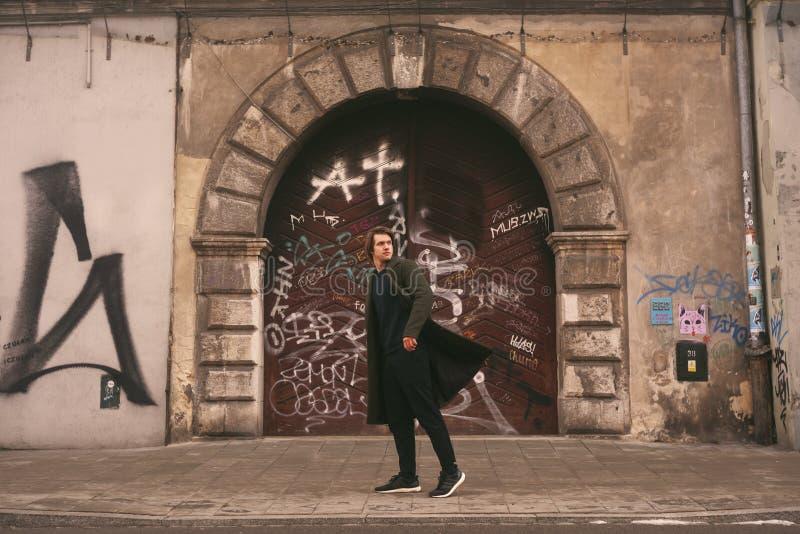 Ein Mann in einem langen Mantel, Reisen zum alten Europa Alte Stadt von Prag, Krakau Modemann geht auf eine Stadtstraße, reist al stockbild