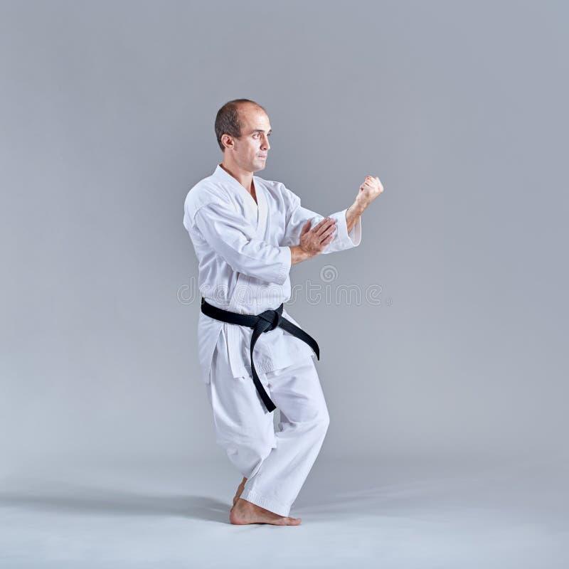 Ein Mann in einem niedrigen Gestell trainiert eine formale Karateübung lizenzfreies stockbild