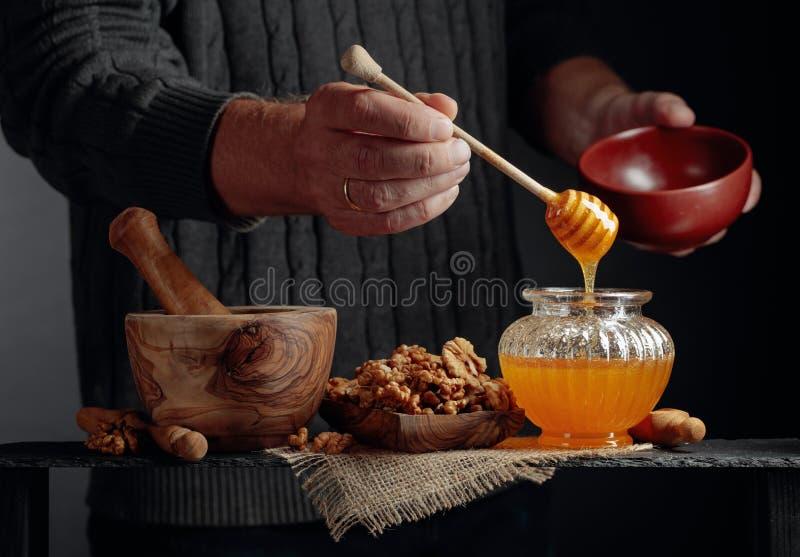 Ein Mann in einem Pullover bereitet ein Frühstück aus Nüssen und Honig zu lizenzfreies stockfoto