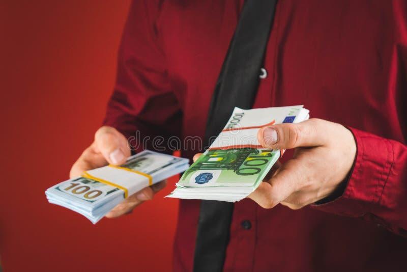 ein Mann in einem roten Hemd mit einer Karte h?lt in seiner Hand ein Pack von Rechnungen auf einem roten Hintergrund stockfoto