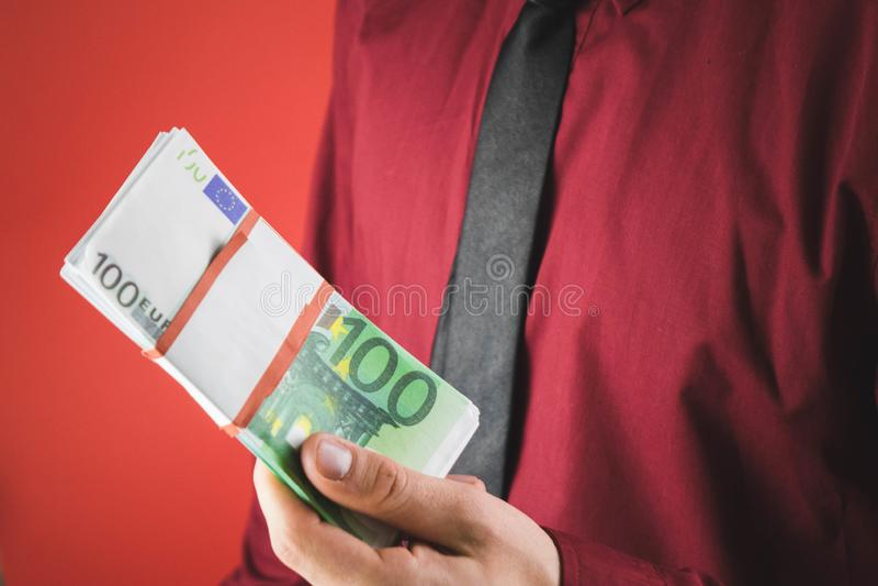ein Mann in einem roten Hemd mit einer Karte h?lt in seiner Hand ein Pack von Rechnungen auf einem roten Hintergrund stockbilder