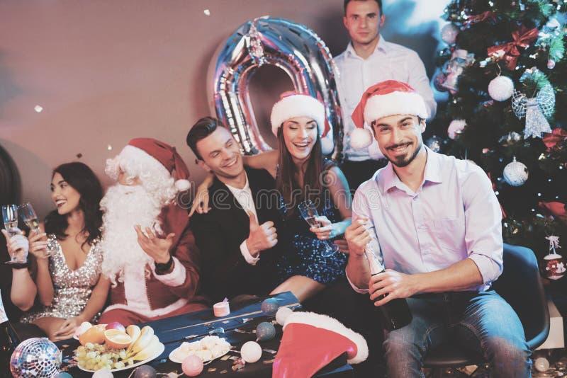Ein Mann in einem Santa Claus-Hut öffnet eine Flasche Champagner Ein Mann ` s sitzen Freunde nahe bei ihm und einem Kerl, der als lizenzfreie stockbilder