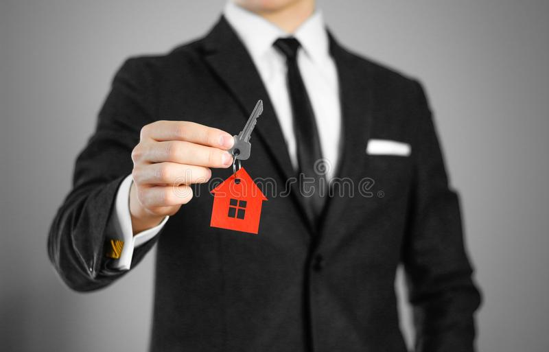 Ein Mann in einem schwarzen Anzug hält die Schlüssel zum Haus Schlüsselringrot lizenzfreie stockfotos