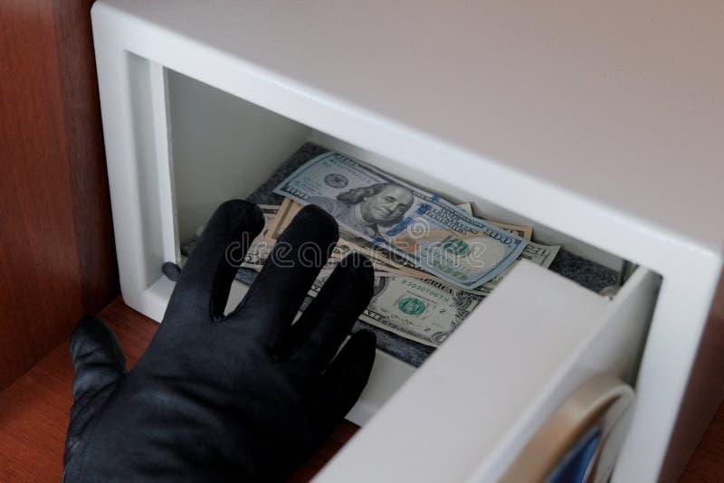 Ein Mann in einem schwarzen Handschuh stiehlt Banknoten von einem Metallsafe mit einem Kombinationsschloß Brechen in ein Sicherhe stockbild
