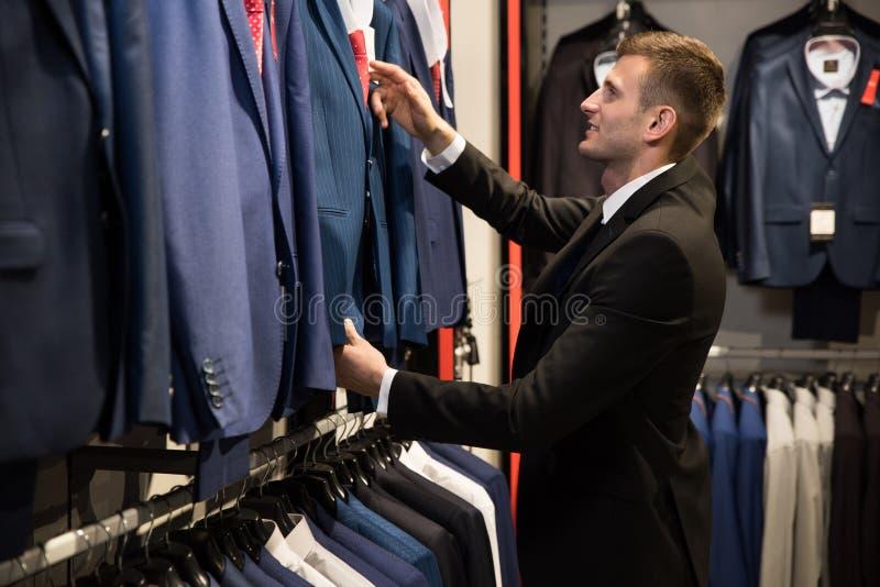 Ein Mann in einem Shop wählt eine Jacke lizenzfreies stockbild