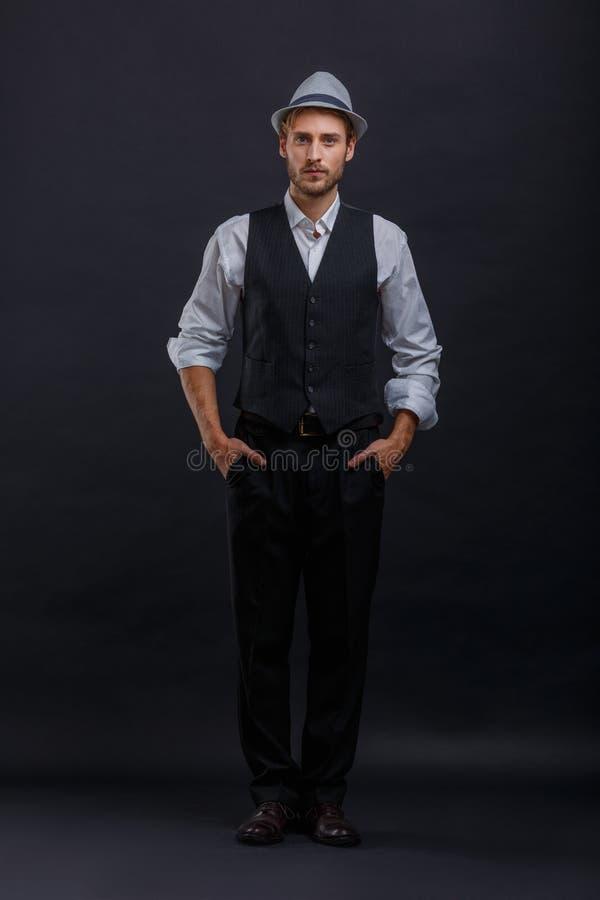 Ein Mann in einem stilvollen Anzug und in einem Hut, Griffe seine Hände in den Taschen Auf einem schwarzen Hintergrund lizenzfreie stockfotografie