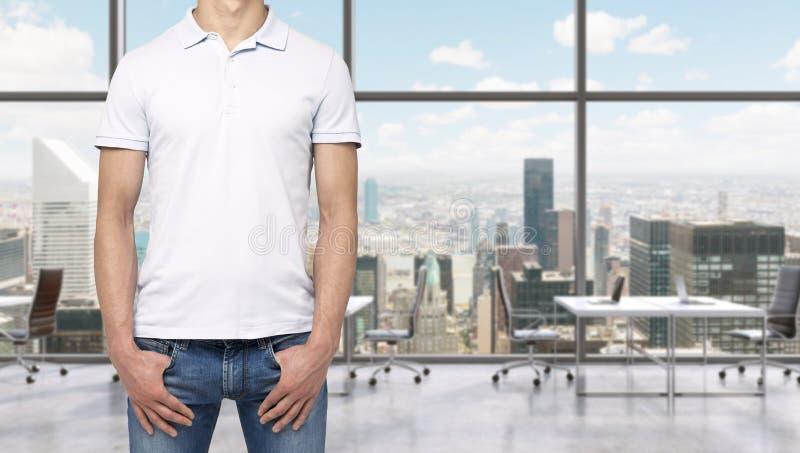 Ein Mann in einem weißen Polohemd und in den Denim hält seine Hände in den Taschen Modernen panoramischen Büroräume in New York C lizenzfreie stockbilder