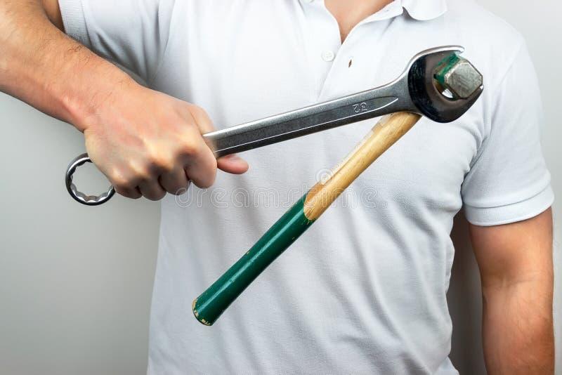 Ein Mann in einem weißen T-Shirt hält einen Schlüssel fest mit einem Hammer, der an ihm hängt lizenzfreies stockbild