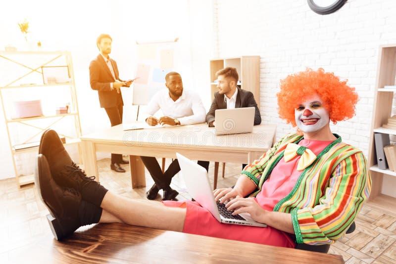 Ein Mann in einer Clownklage, die oben an seinem Schreibtisch, seine Füße auf dem Tisch sitzt lizenzfreie stockbilder