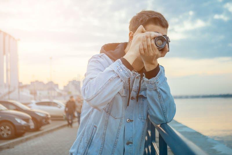 Ein Mann in einer Denimjacke mit einer Weinlesefilmkamera lizenzfreies stockbild