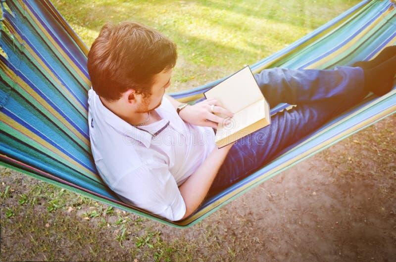 Ein Mann in einer Hängematte liest ein Buch lizenzfreies stockbild
