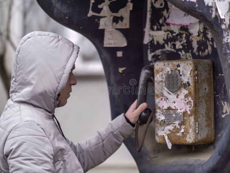 Ein Mann in einer hellen Jacke in einer Haube nennt ein altes Stra?enm?nztelefon lizenzfreies stockbild