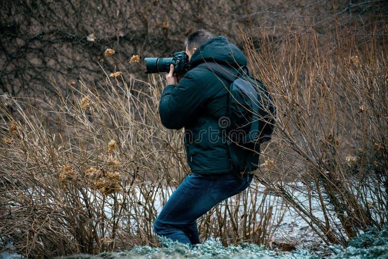 Ein Mann in einer Jacke mit einer Haube und einem Aktenkoffer auf seinem zurück, eine Kamera halten lizenzfreies stockbild