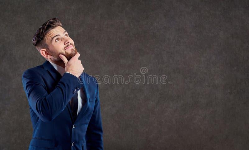 Ein Mann in einer Klage denkt über einer Frage lizenzfreie stockfotos