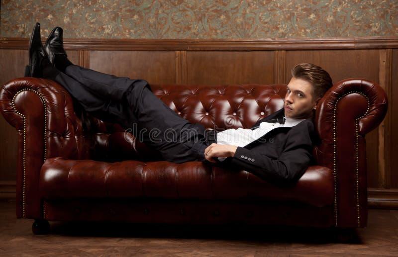 Ein Mann in einer Klage, die auf der Couch liegt lizenzfreies stockfoto