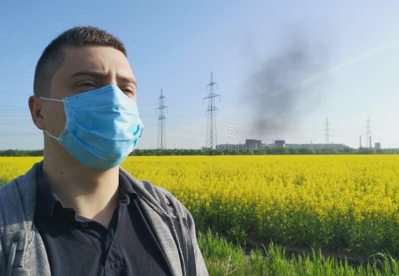 Ein Mann in einer medizinischen Maske vor dem hintergrund der Anlage Das Konzept der Umweltverschmutzung, ?kologie stockbilder