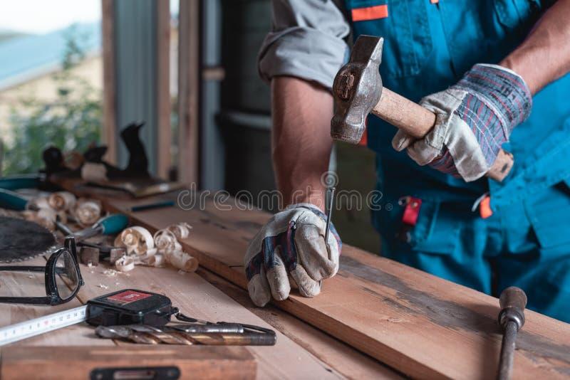 Ein Mann Erbauer im Overall und in den Handschuhen hämmert einen Nagel in eine Nahaufnahme des hölzernen Brettes, Dach, Bau, Haup stockfotografie