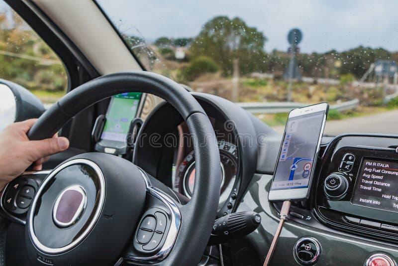 Ein Mann fährt ein Auto unter Verwendung zwei Navigatoren für den Weg lizenzfreies stockfoto