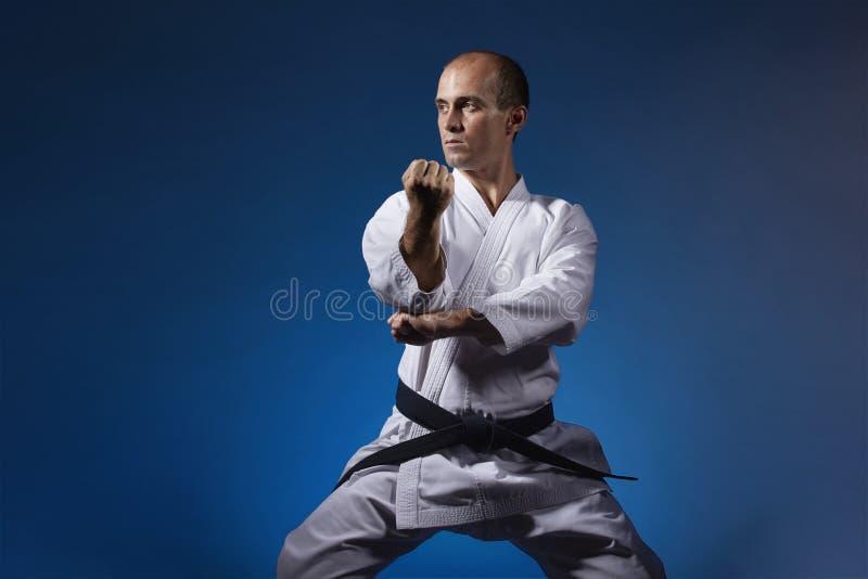 Ein Mann führt formale Übungen von Karate auf einem blauen Hintergrund durch lizenzfreies stockbild