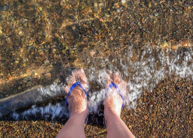 Ein Mann geht barfuß auf den Strand Menschliche Beine im Wasser Wellen schlugen auf den Beinen des Mannes lizenzfreie stockbilder