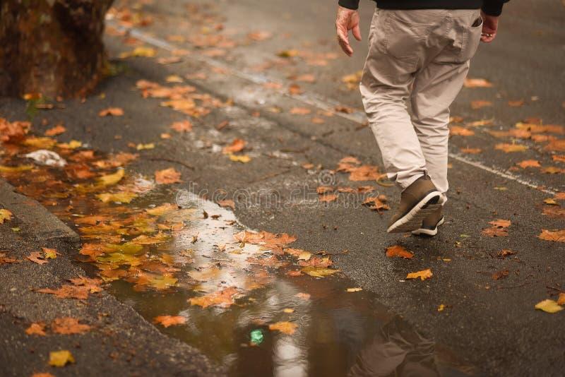 Ein Mann geht in den Regen ohne einen Regenschirm lizenzfreies stockbild