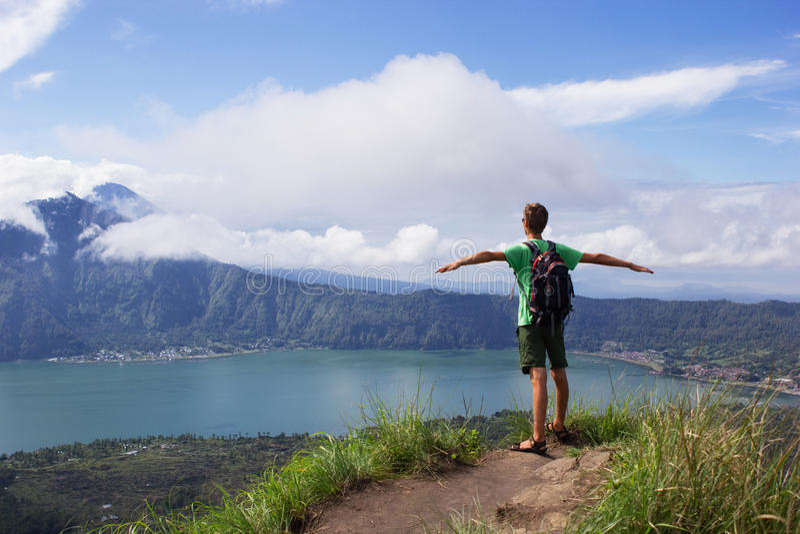 Ein Mann genießt Vulkanseeblick mit blauem Himmel der Wolken lizenzfreie stockfotos