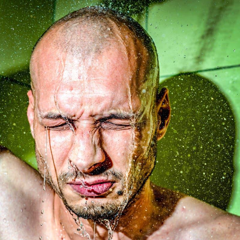 Ein Mann gibt sich eine kalte Dusche nach der Arbeit, um sich nach hartem frustriertem und nervösem Tag an seinem Jobabschluß obe lizenzfreies stockbild