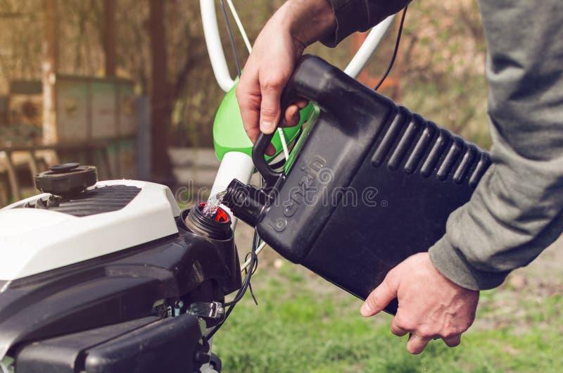 Ein Mann gießt Benzin vom Kanister in den Landwirtbehälter stockfotografie