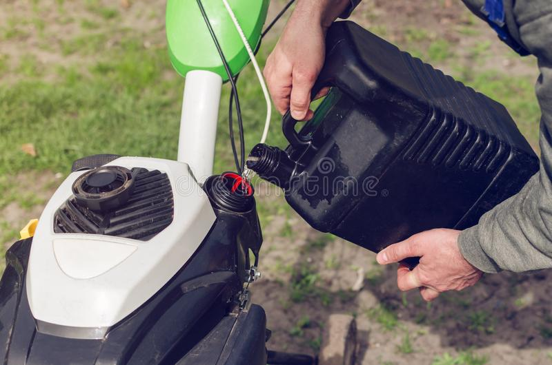 Ein Mann gießt Benzin vom Kanister in den Landwirtbehälter lizenzfreies stockfoto