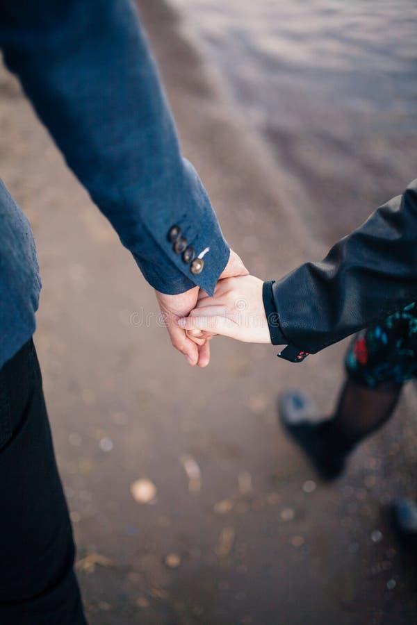 Ein Mann hält die Hände eines Mädchens und der Führungen entlang dem Fluss stockbild