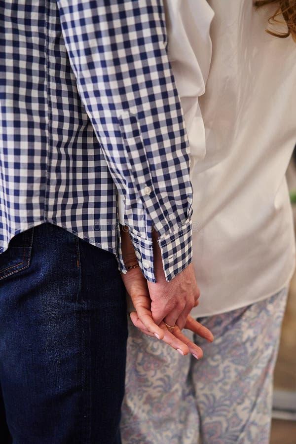 Ein Mann hält die Hand des Mädchens mit seinem Ehering stockbild
