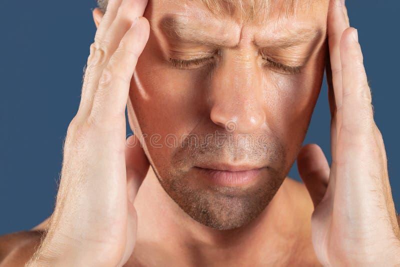 Ein Mann hält seine Hände auf seinem Kopf auf blauem Hintergrund Kopfschmerzen oder Migräne stockfoto