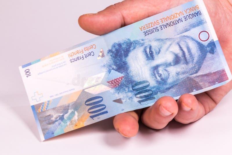Ein Mann hält in seiner Hand eine Schweizer Banknotennahaufnahme stockfotografie