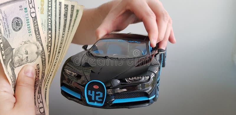 Ein Mann hält in seiner Hand im Luft schwarzen Auto-Metallspielzeug Bugattis Chiron, während andere Person ihm ein Bündel Geld gi lizenzfreie stockfotografie