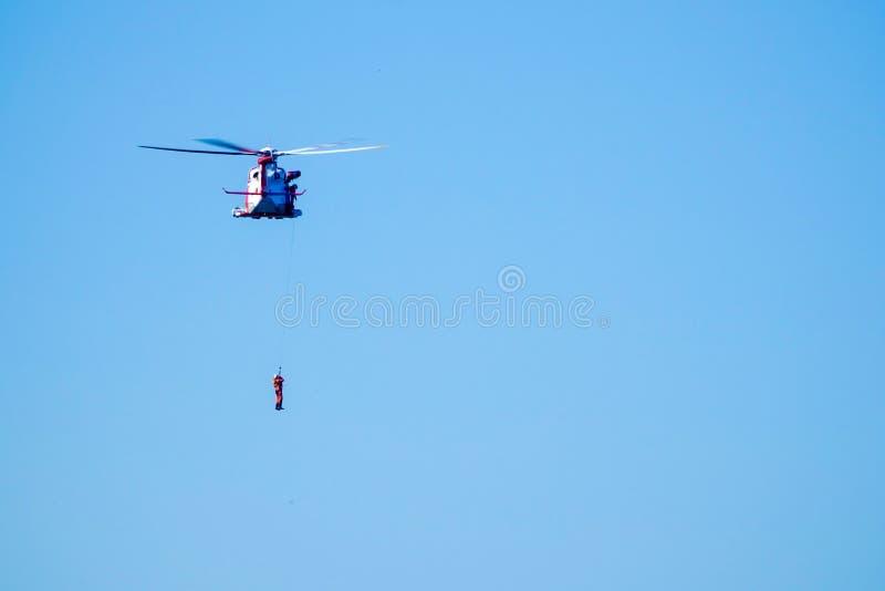 Ein Mann hängt von einem Hubschrauber stockbild