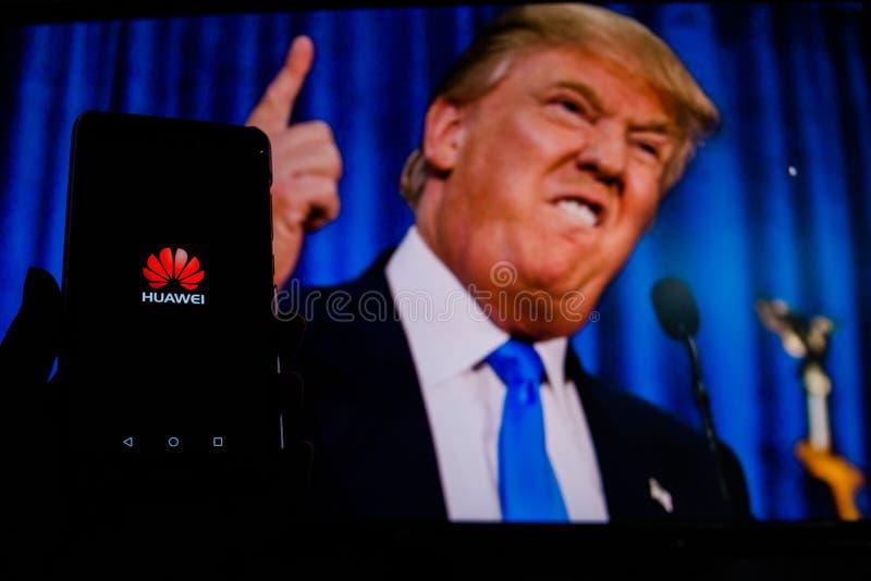 Ein Mann h?lt AndroidSmartphone, das das Logo f?r den Google-Spielspeicher vor dem Bild von Donald Trump zeigt stockfoto