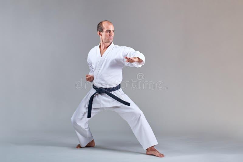 Ein Mann im karategi bildet eine formale Karateübung auf einem grauen Hintergrund aus stockfotografie