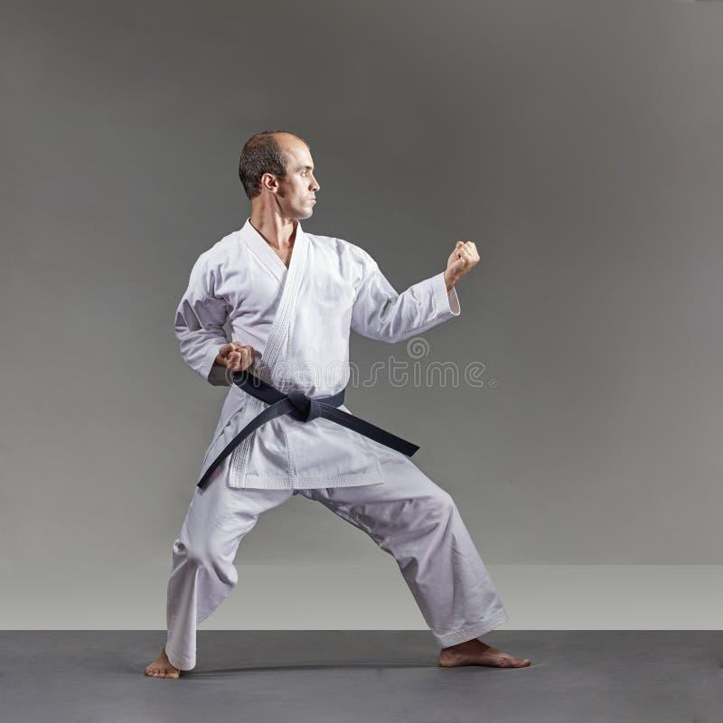 Ein Mann im karategi bildet formale Karateübungen auf einem grauen Hintergrund aus stockbilder