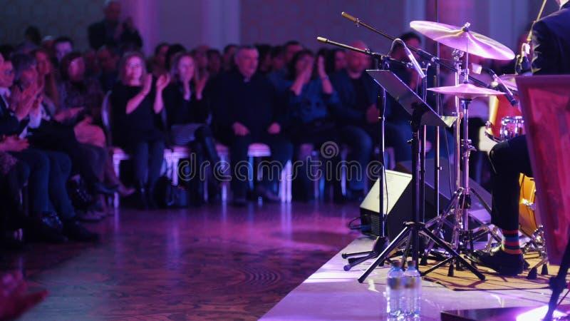 Ein Mann im Kostüm, das Trommeln am Jazzkonzert spielt Das Publikum, das ihre Hände klatscht stockfotos