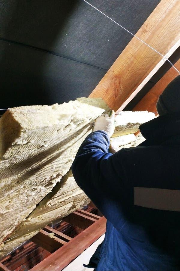 Ein Mann installiert eine Wärmedämmungsschicht eines thermischen Dachs - unter Verwendung der Platten der Mineralwolle und brin stockfotografie