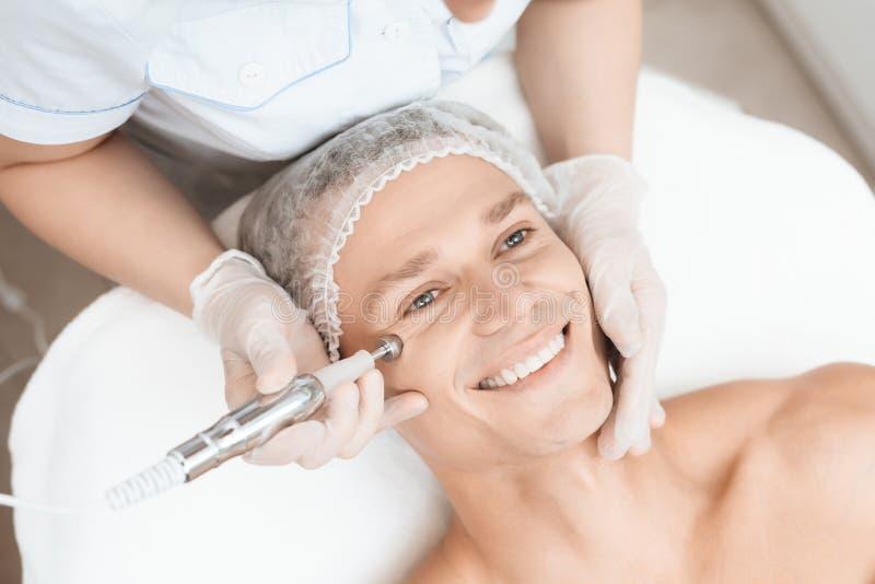 Ein Mann kam zur Laser-Haarabbaugesichtsbehandlung Doktor führt ihn im Gesicht mit einem modernen Laser-epilator lizenzfreie stockfotos