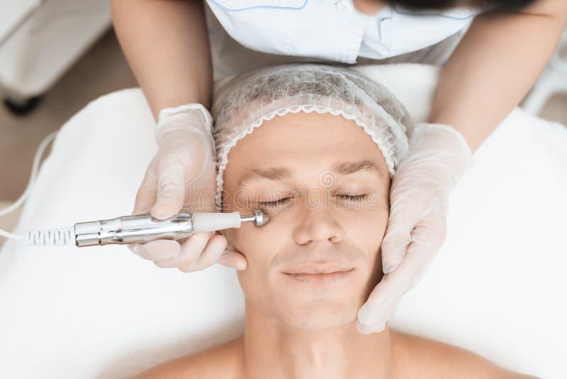 Ein Mann kam zur Laser-Haarabbaugesichtsbehandlung Doktor führt ihn im Gesicht mit einem modernen Laser-epilator lizenzfreies stockfoto